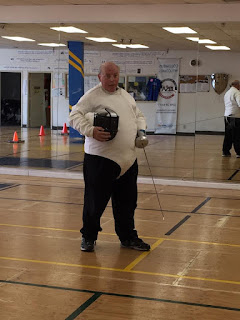 William at Fresno Fencing Academy in fencing jacket holding a competition epee sword and a fencing face mask.