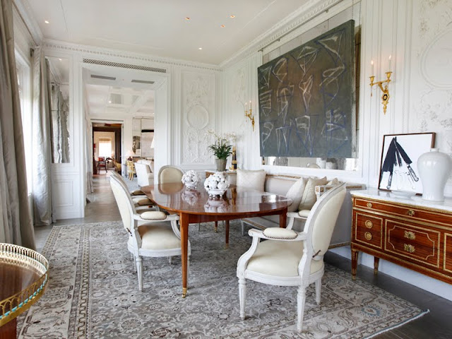 Dining room with large area rug, wood table, white louis xiv chairs, white molded walls and modern art