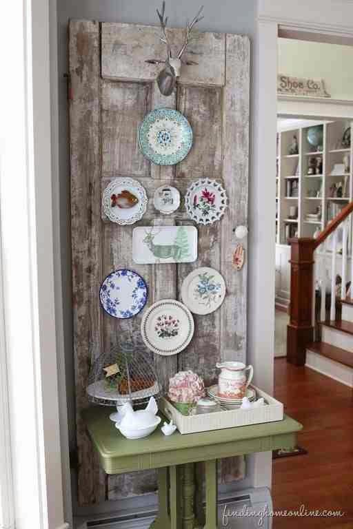Kolorowe talerze na starych drzwiach vintage. Rustykalna dekoracja wnętrz.