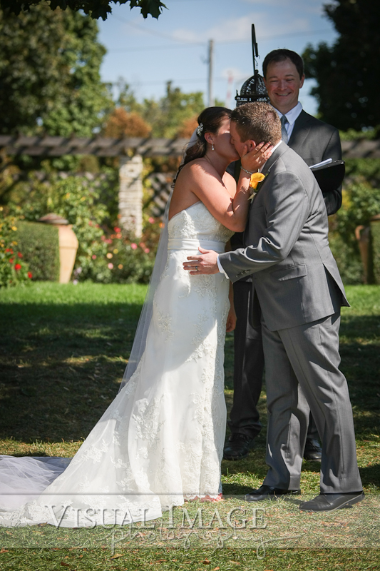 Bride and groom sharing first kiss during wedding ceremony at Frame Park