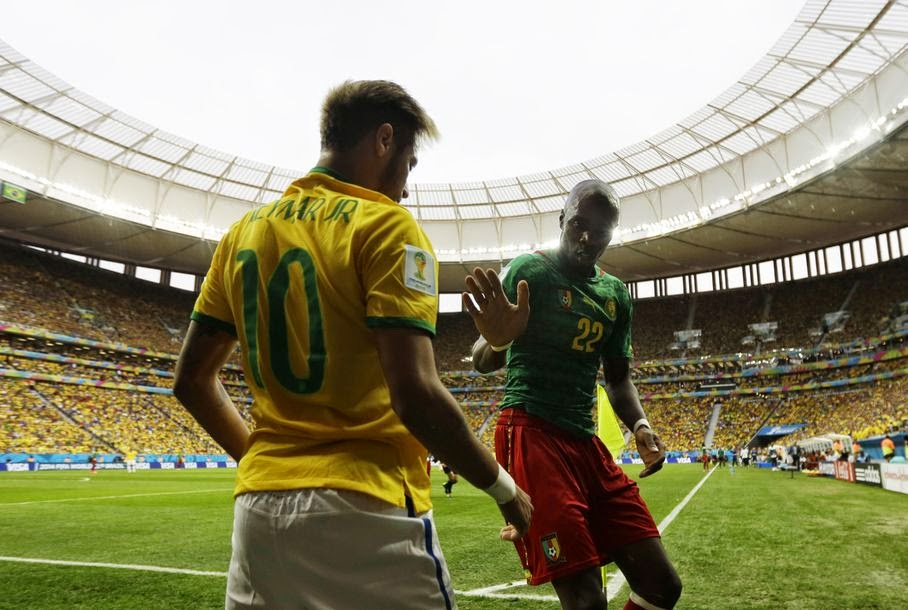Cameroon's Allan Nyom tries to shake hands with Brazil's Neymar after pushing him to the ground in the corner during the group A World Cup soccer match between Cameroon and Brazil at the Estadio Nacional in Brasilia, Brazil, Monday, June 23, 2014.