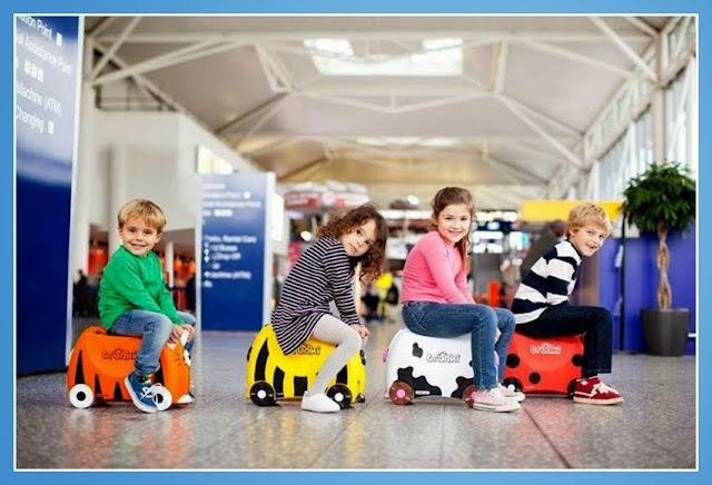 Niños montados en maletas Trunki en el aeropuerto