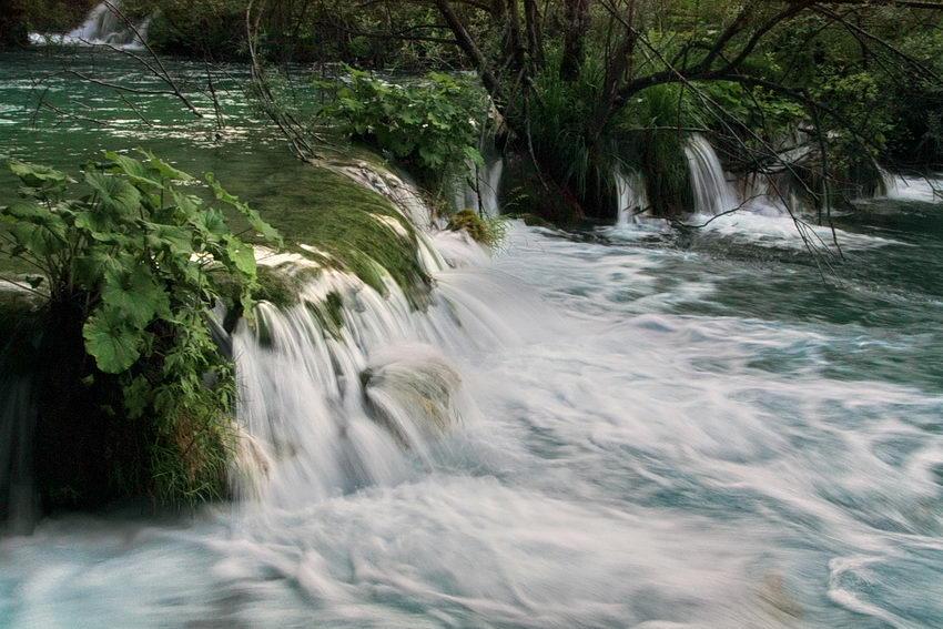 Foto de uma cascata mostrando e efeito da velocidade da água pela desfocagem originada por baixa velocidade do obturador da câmara fotográfica