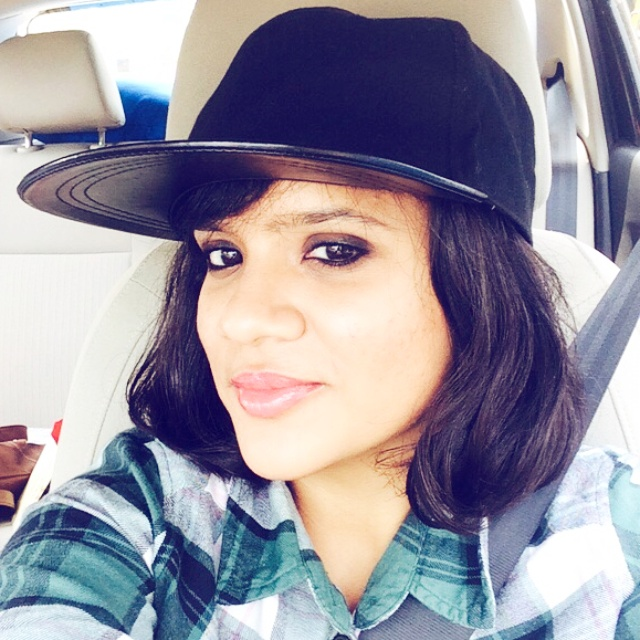 Dayle Pereira, blogger at Style File takes a car selfie wearing plaid, a cap and kohl rimmed eyes