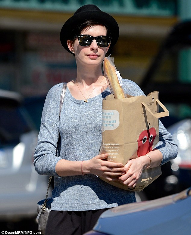 what could actress Anne Hathaway have in that bag with a french bread sticking out of it?
