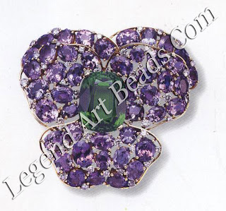 Two of Verdura's flower jewels: a pansy brooch with a large 43 carat peridots and tanzanites;