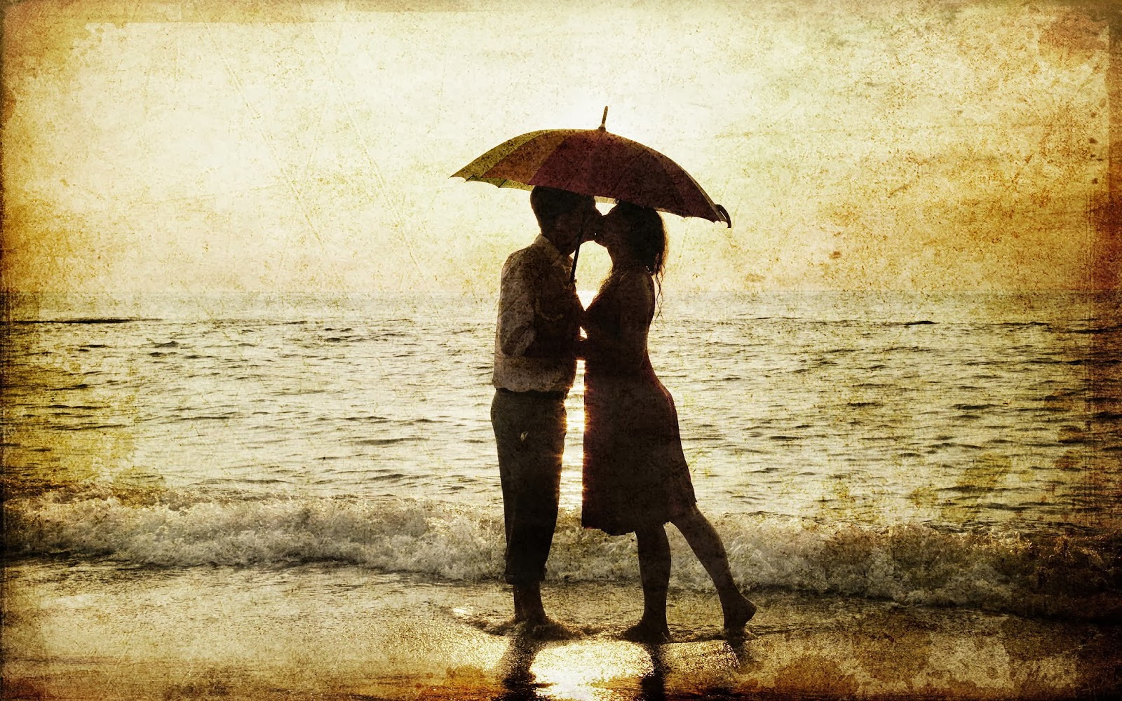 Boy-and-girl-kiss-at-seashore-under-umbrella-photos-download.jpg