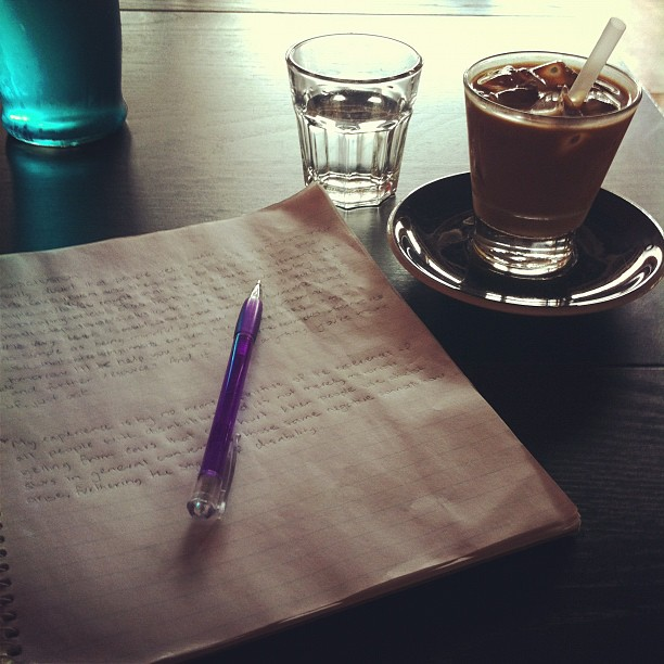 Photo of my study notebook and an iced coffee on a table at a local café.