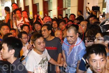 """上图: 红圈者里的人是香港黑社会组织""""和胜和""""的小头目大鬼。 2014年10月3日,香港大批支持雨伞运动的市民包围了在旺角现场的黑社会组织""""和胜和""""小头目大鬼(红圈者),要求警方严正执法。(潘在殊/大纪元)"""
