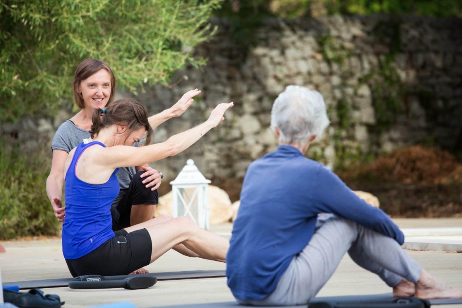 Pilates instructor helping students at the pool