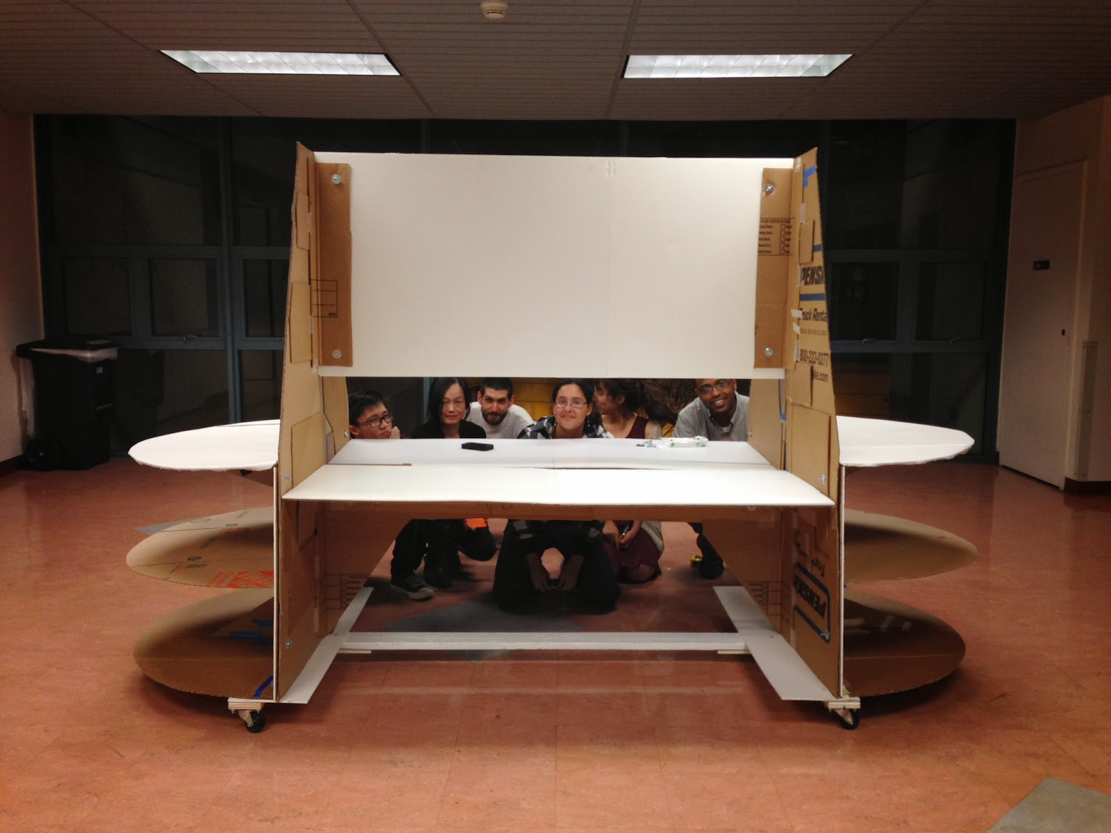 Image shows a frontal view of the full-scale cardboard prototype for the exhibit. Students kneel behind it and peer through the panel.