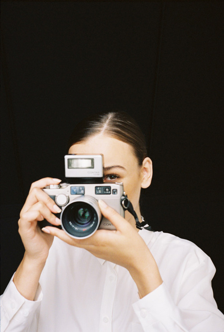 Girl behind a camera, slicked back pony tail, minimalism, say cheese