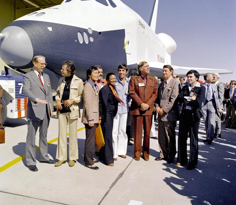 "In 1976, NASA's space shuttle Enterprise rolled out of the Palmdale manufacturing facilities and was greeted by NASA officials and cast members from the 'Star Trek' television series. From left to right they are: NASA Administrator Dr. James D. Fletcher; DeForest Kelley, who portrayed Dr. ""Bones"" McCoy on the series; George Takei (Mr. Sulu); James Doohan (Chief Engineer Montgomery ""Scotty"" Scott); Nichelle Nichols (Lt. Uhura); Leonard Nimoy (Mr. Spock); series creator Gene Roddenberry;  U.S. Rep. Don Fuqua (D.-Fla.); and, Walter Koenig (Ensign Pavel Chekov). NASA is mourning the passing today, Feb. 27, 2015, of actor Leonard Nimoy, most famous for his role as Star Trek's Vulcan science officer Mr. Spock. The sci-fi classic served as an inspiration for many at NASA over the years, and Nimoy joined other cast members at special NASA events and worked to promote NASA missions, as in this 2007 video he narrated before the launch of the Dawn mission to the asteroid belt. Nimoy also was there for the 1976 rollout of the shuttle Enterprise, named for the show's iconic spacecraft."