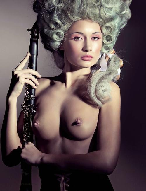 jeune femme nue mince avec une clarinette et une perruque renaissance