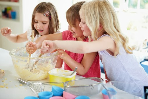 three young girls baking mixing cake batter