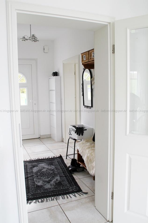 Blick in den Flur mit Garderobe aus Holz und schwarz weißen Wohnaccessoires, Teppich und Fell und Kissen auf der Holzbank