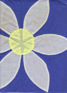 Appliqué of a flower on blue background. White petals show through yellow center.