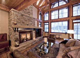 Traditional Living Room with Fluffy Sofas and the Glass Table facing the Stone Rustic Fireplace Mantels