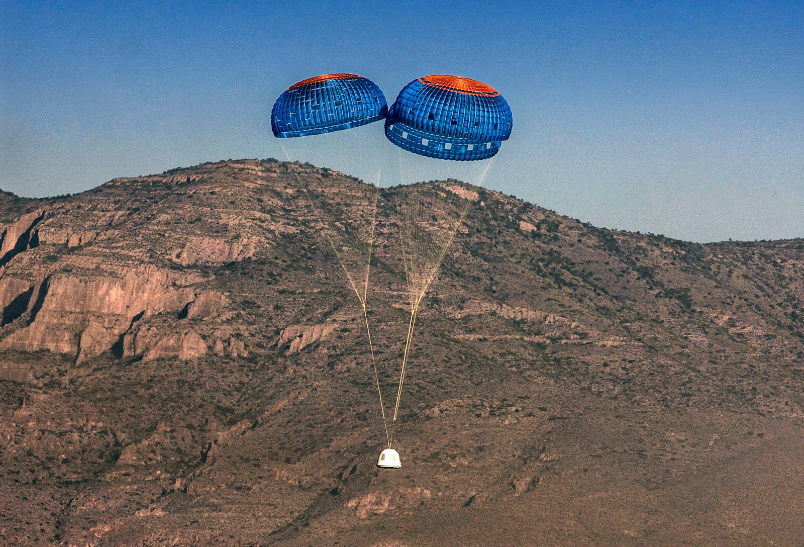 After a clean separation from the propulsion module, the New Shepard crew capsule descends to a gentle landing in the west Texas desert. Credit: Blue Origin