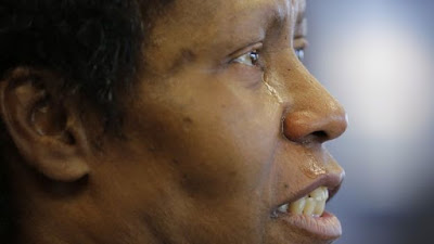 Brown woman facing away from camera. Profile of her face and crying.