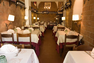 Trattoria Polese's dining room with white table cloths and romantic lighting.