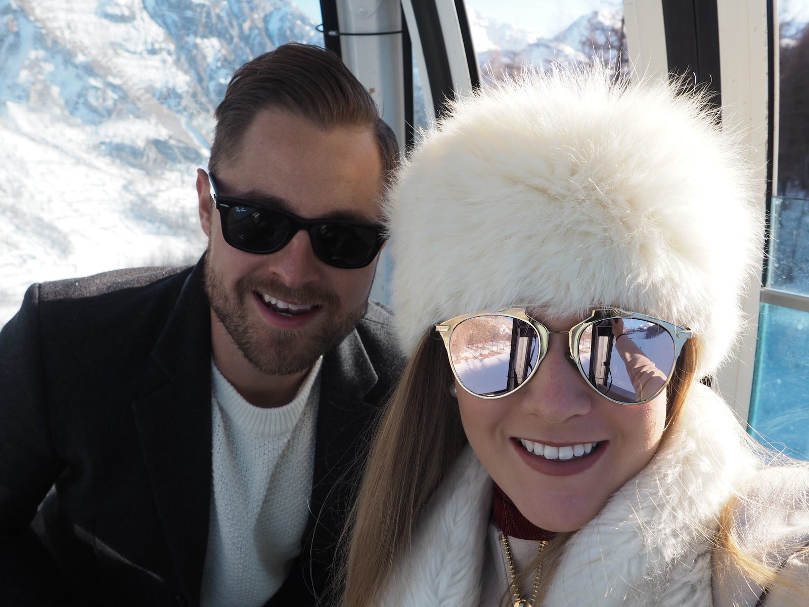 Smiling couple sitting in cable car against snowy mountains, Val d'Isere, France