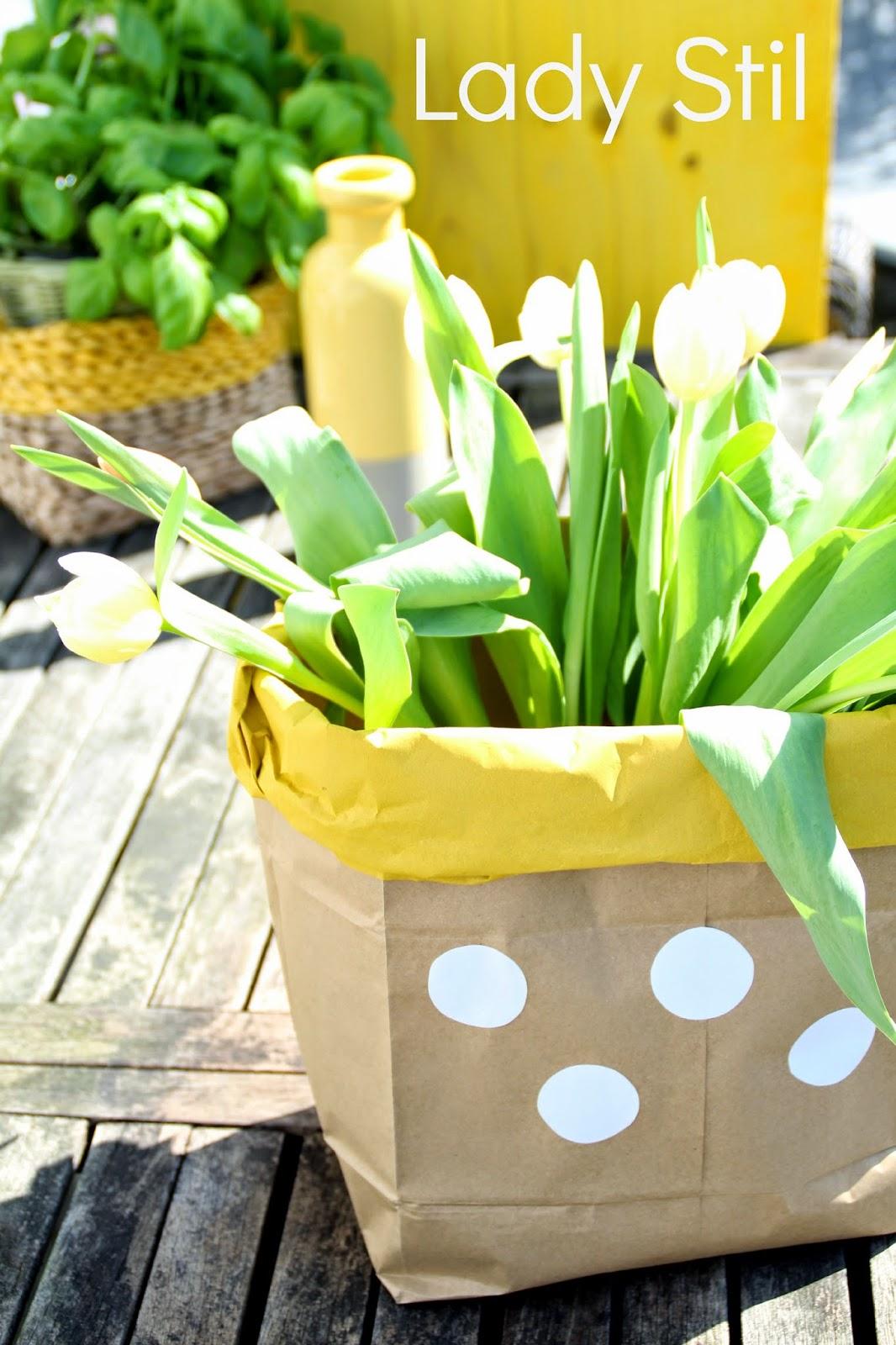 Paperbag in gelb-braun mit weißen Tulpen im Hintergrund gelbe Vase und Korb mit Basilikum