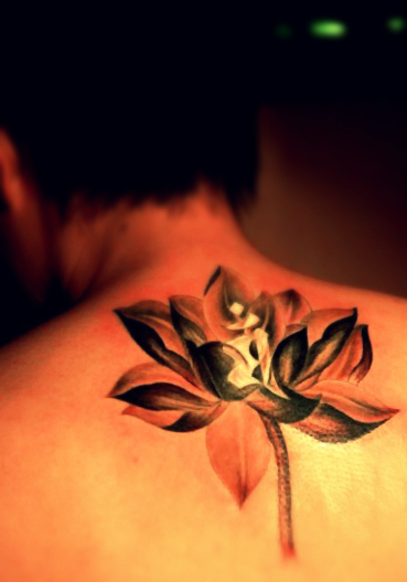 A golden and shining lotus flower tattoo on the back