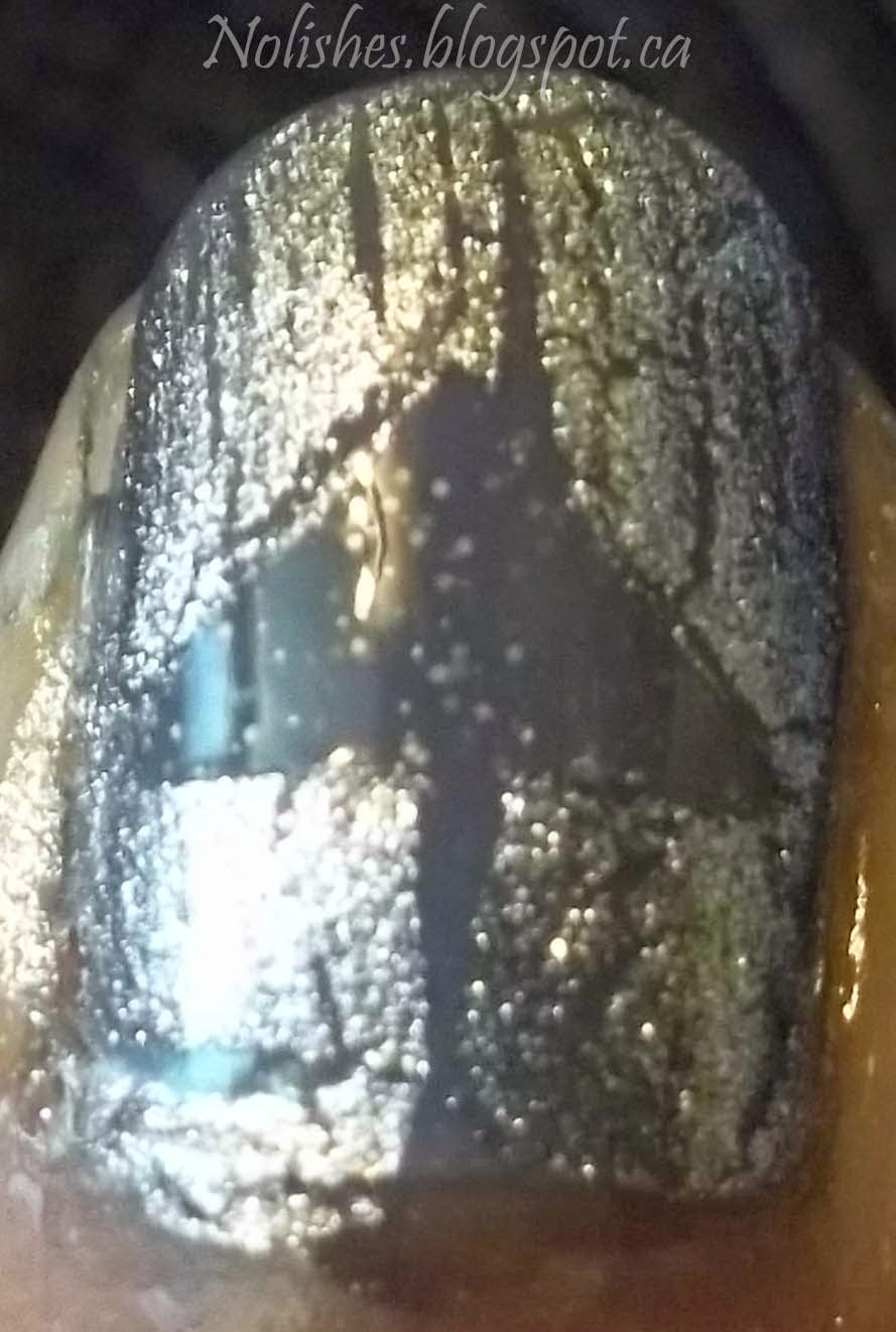 Thumbnail polished with grey polish covered in silver shatter polish, with a grey triangle in the centre.