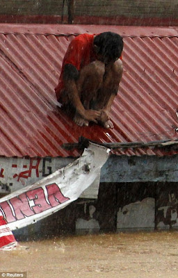 A man waits for rescuers on the rooftop of a house swamped with floodwaters in Marikina, Metro Manila
