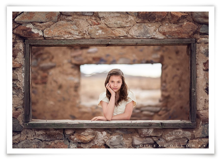 photo de Lisa Holloway représentant le portrait en plan large d'une jeune fille au travers d'une fenetre d'une maison abandonnée