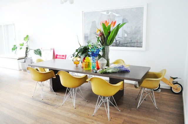 Dining room with wood floors, yellow Eames chairs around a modern dark wood table