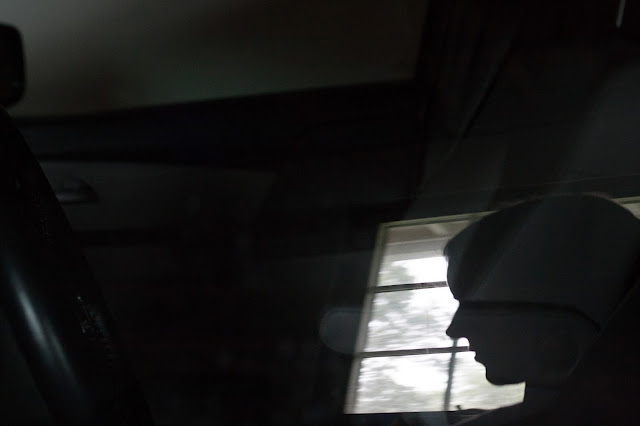 silhouette of a woman's face reflected in car window