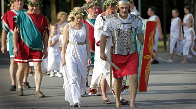 Čovek u rimskoj uniformi i grupa muškaraca i žena u rimskim odorama