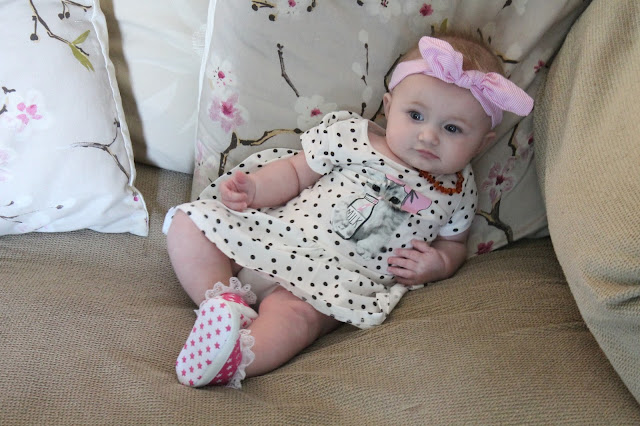 Baby slouched on sofa wearing polka dot dress with a picture of a cat drinking milk from a bottle through a straw on it. Pink trainers with star pattern and a pink striped bunny ear headband.