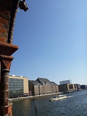 Rotes Ziegelmauerwerk, Wasserspeier, Gebäude, blaues Spreewasser mit Schiff, blauer Himmel