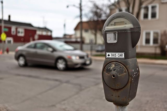 One parking meter pointing at two cars near downtown Milwaukee.