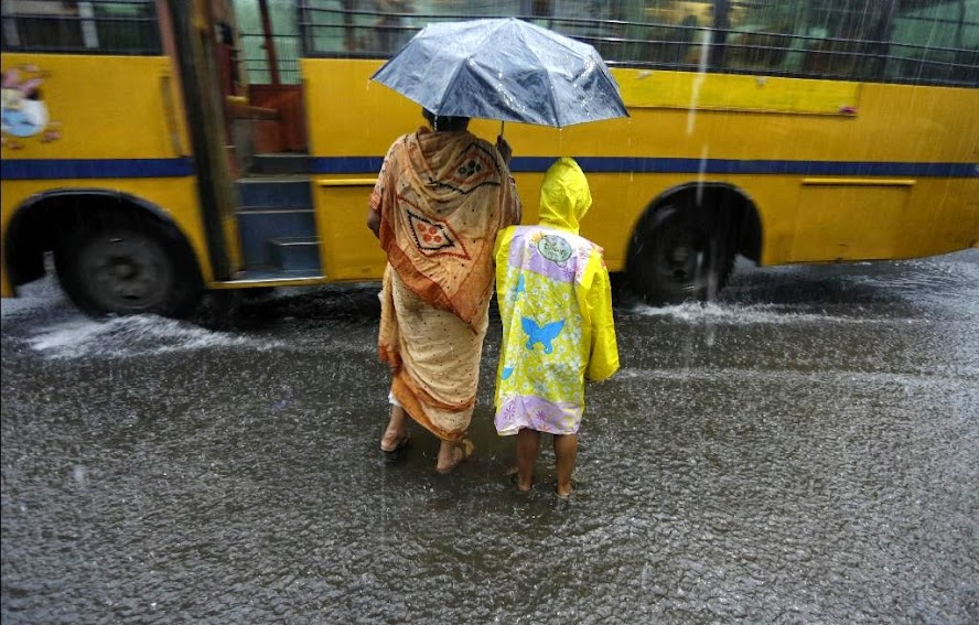 A woman accompanies a child home from school in the rain in Kolkata, India, Wednesday, July 2, 2014. Normal traffic was affected in several areas of the city because of overnight rainfall that caused water-logging, according to news reports.