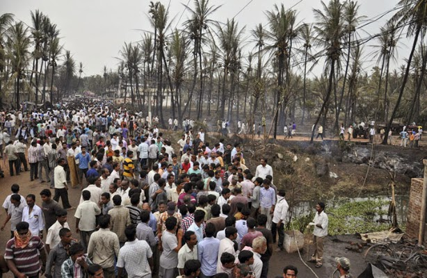 People gather at the site of a pipeline explosion in Nagaram village, India, Friday, June 27, 2014. A state-owned gas pipeline exploded and burst into flames Friday, killing at more than a dozen people, destroying homes and forcing the evacuation of neighboring villages in the southern Indian state of Andhra Pradesh, authorities said.