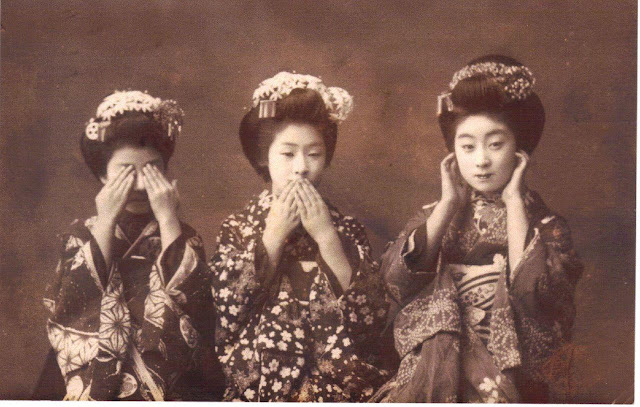 Cepia toned photograph which A Japanese post card from the late 19th century, which shows three geisha imitating the Three Wise Monkeys. Left to right they are: Mizaru (see no evil), Iwazaru (speak no evil), and Kikazaru (hear no evil).