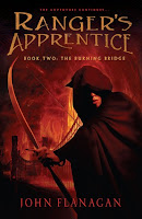 the cover of The Burning Bridge by John Flanagan book two in the ranger's apprentice series shows a cloaked boy with a drawn boy with a bridge on fire behind him
