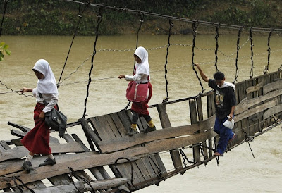 Indonesian children make perilous journey to school over collapsed bridge