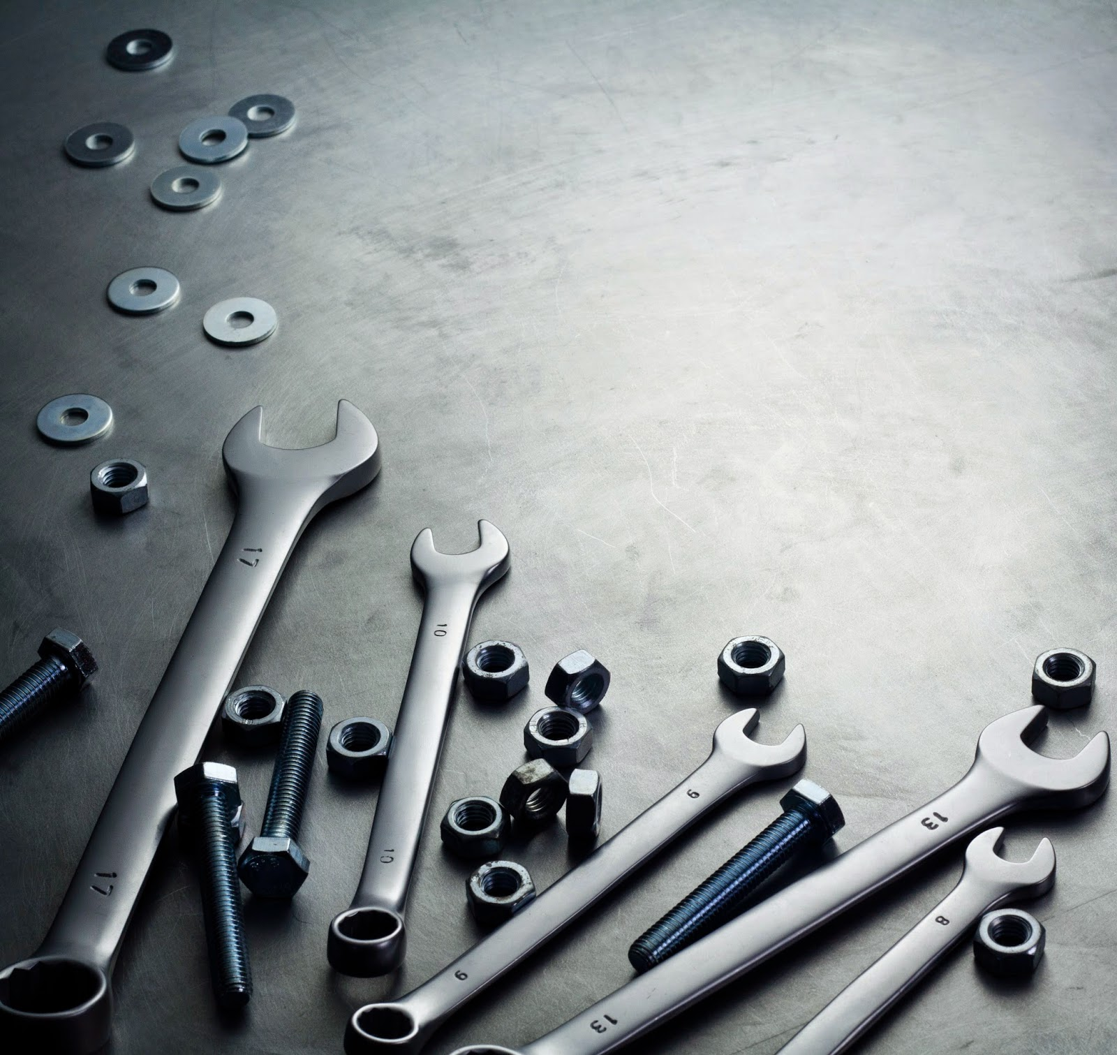 Wrenches and hardware on metal surface