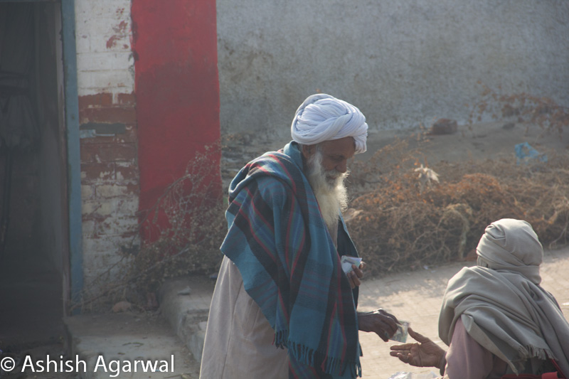 Elderly sikh man paying a vendor at a railway station for some service tendered