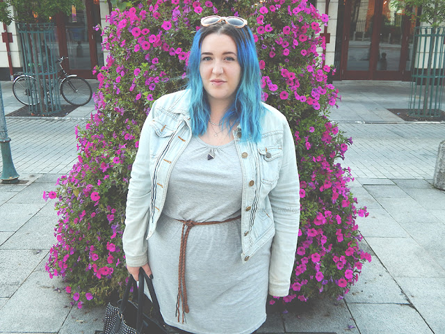 Girl with blue hair standing in front of purple flowers