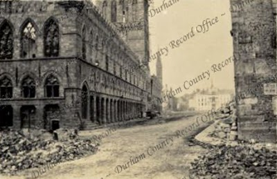 Shell-damaged buildings and streets, taken by PHB Lyon, captioned: Ypres, the Cloth Hall from the west, Belgium, 14 May 1915 (D/DLI 7/424/2(66))