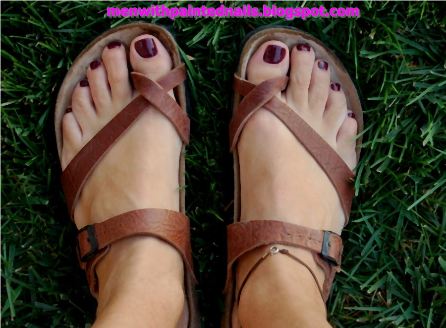 Male Foot With Birkenstock Tobago Sandals And Dark Red Nail Polish And Anklet