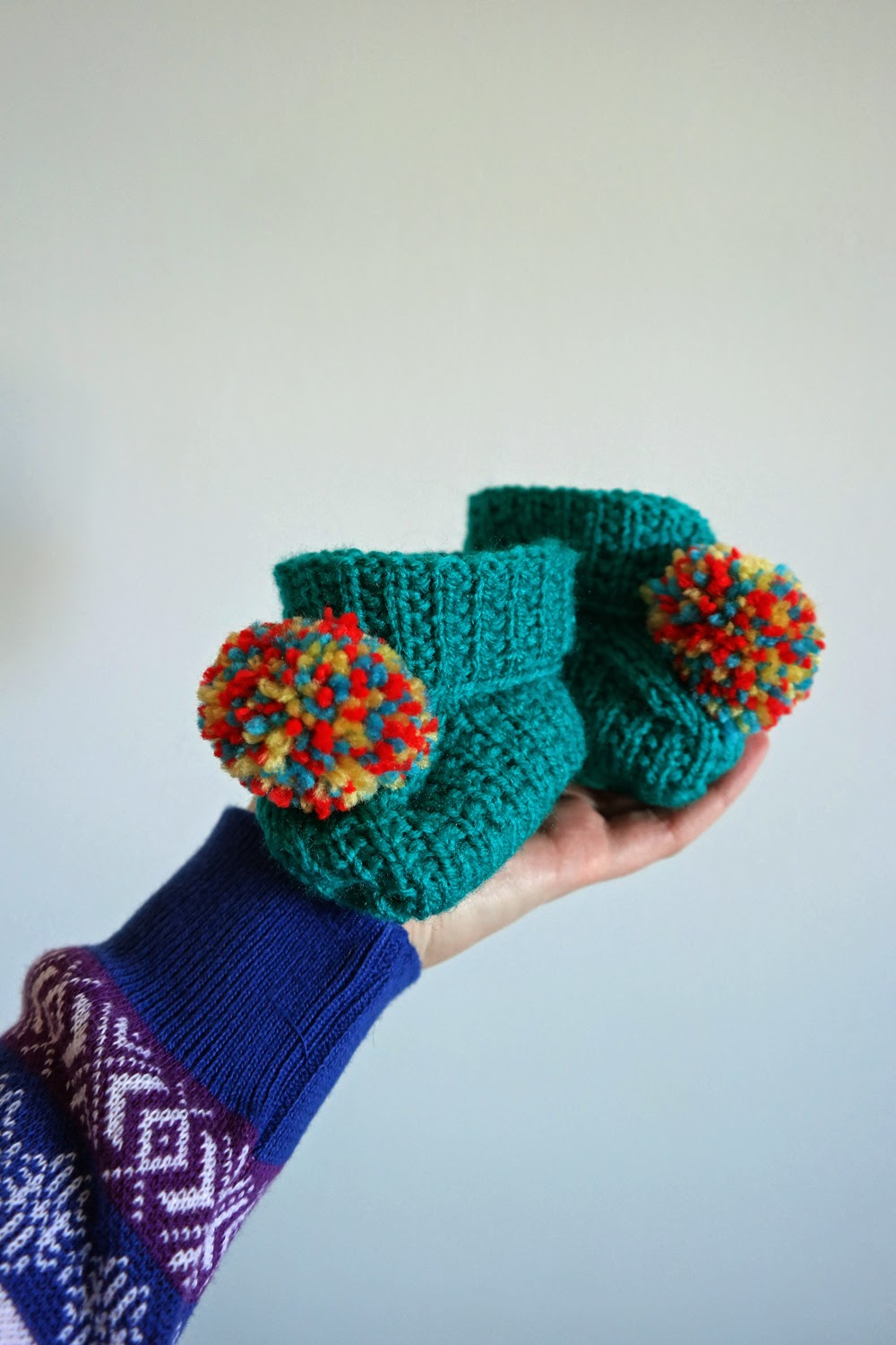 Baby booties with pom-poms on them