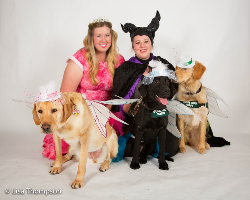 puppy raisers Megan and Haley with their puppies Paris, Denmark and Dinah dressed as Flora, Fauna and Merryweather, the three godmothers in Sleeping Beauty.