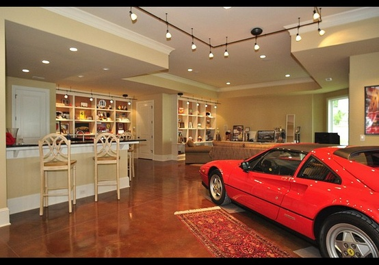 Here The Ferrari Is Right At Home Alongside A Wet Bar And Seating Area Polished Stained Concrete Hand Knotted Rug IN THE GARAGE Posh